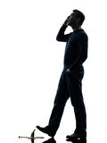 Careless man walking silhouette. One  man careless man walking on the telephone in silhouette studio  on white background Stock Image
