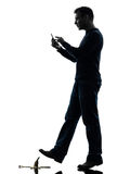 Careless man walking silhouette. One man careless man walking on the telephone in silhouette studio on white background Royalty Free Stock Photo