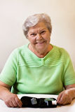 Careless senior woman wants to measure blood sugar Stock Photography
