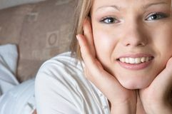 Careless smiling. Facial closeup of smiling pretty girl laying on sofa Royalty Free Stock Photos