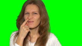 Careless woman picks her nose with finger. Female scratching finger in nose stock video footage