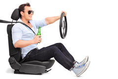 Careless young man drinking and driving. Careless young man driving and holding a bottle of beer isolated on white background Royalty Free Stock Photo