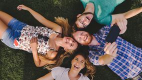 Careless young people having a laugh outdoors lying in grass. Careless young people having a laugh outdoors while  lying in grass Royalty Free Stock Images