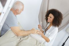 Carer administering medication to patient. Carer Royalty Free Stock Photo