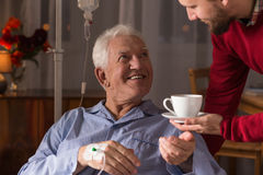 Carer assisting incurable ill man. Male carer assisting incurable ill senior man Stock Photos