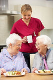 Carer drinking tea with two elderly woman Royalty Free Stock Photos