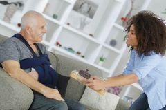 Carer giving breakfast to senior patient. Woman royalty free stock photography