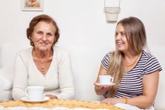 Carer having a cup of tea with an elderly woman Stock Photo