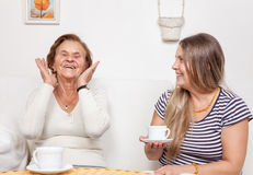 Carer having a cup of tea with an elderly woman Royalty Free Stock Photos