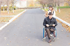 Smiling carer pushing an old man in a wheelchair stock photo image - Woman Pushing An Elderly Man In A Wheelchair Stock Image
