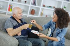 Carer helping injured elderly patient royalty free stock images