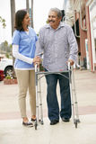 Carer Helping Senior Man To Use Walking Frame Royalty Free Stock Image