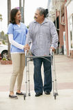 Carer Helping Senior Man To Use Walking Frame Stock Images