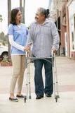 Carer Helping Senior Man To Use Walking Frame Stock Images