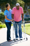 Carer Helping Senior Man With Walking Frame Stock Photos