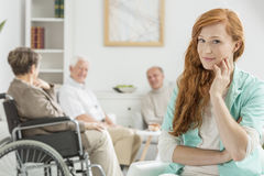 Carer in nursing home. Young pretty carer in nursing home and patients behind her stock image