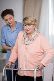 Carer and older woman. Female carer helping older women with handicap Royalty Free Stock Images
