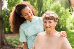 Carer and older woman. Young pretty helpful carer and senior woman stock photo