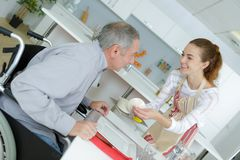 Carer passing meal to elderly man wearing sling stock photography