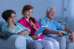 Carer reading book. To elderly woman, senior men watching television stock images