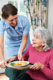 Carer Serving Lunch To Senior Woman Royalty Free Stock Photo