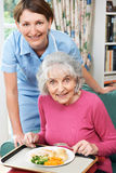 Carer Serving Lunch To Senior Woman Royalty Free Stock Photography