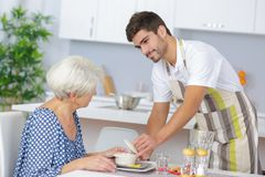 Carer serving lunch to senior woman stock images