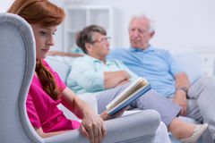 Carer sitting in armchair. With book, mature couple in background royalty free stock photo