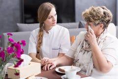 Carer supporting ill, sad senior. Good carer supporting ill and sad senior woman royalty free stock photo