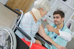 Carer supporting old woman with health afflictions stock photography