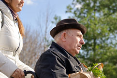 Carer taking an elderly man grocery shopping. Close up portrait of female carer taking an elderly men in wheelchair grocery shopping as they return together with Royalty Free Stock Photography