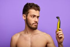 Cares about hygiene, man is checking a new shaver stock photos