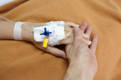 Caress for the sick. Hand holding patient hand in the hospital Stock Photography
