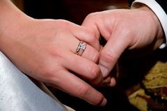 Caressing Hands. A wedding ring on the hand of a newly married bride. The groom caresses her hand stock photos