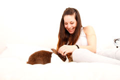 Caressing a rabbit in bed Stock Image