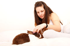 Caressing a rabbit in bed Royalty Free Stock Photos