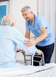 Caretaker Assisting Senior Man To Use Walking. Male caretaker assisting senior men to use walking frame in bedroom at nursing home stock photos