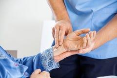 Caretaker Checking Pulse Of Senior Woman. Cropped image male caretaker checking pulse of senior women at nursing home stock images