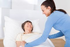 Caretaker covering senior woman with blanket. Young female caretaker covering senior women with blanket in nursing home stock photography