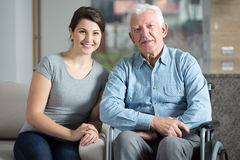Caretaker and elderly man. Young pretty female caretaker and elderly men on a wheelchair Royalty Free Stock Images