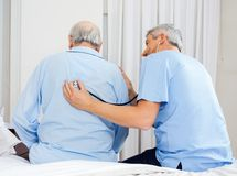 Caretaker Examining Senior Man's Back Stock Photo