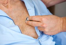 Caretaker Examining Senior Man's Chest With. Cropped image of male caretaker examining senior man's chest with stethoscope at nursing home stock image