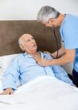 Caretaker Examining Senior Man With Stethoscope. Male caretaker examining senior men with stethoscope in bedroom at nursing home royalty free stock image