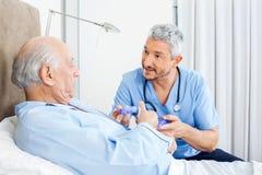 Caretaker Explaining Prescription To Senior Man. Male caretaker explaining prescription to senior men in bedroom at nursing home royalty free stock photography