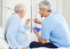 Caretaker Guiding Prescription To Senior Man Stock Image
