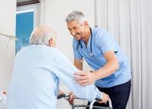 Caretaker Helping Senior Man To Use Walking Frame. Smiling male caretaker helping senior men to use walking frame in bedroom at nursing home royalty free stock photo