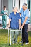 Caretaker Helping Senior Woman To Use Walking Royalty Free Stock Images