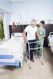 Caretaker Looking At Senior Patient Using Walker. Happy caretaker looking at senior male patient using walker in rehab center stock photo