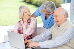 Caretaker Looking At Senior Woman By Man Using. Male caretaker looking at senior women by men using laptop at nursing home stock photos