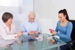 Caretaker Playing Cards With Senior Couple Royalty Free Stock Photo